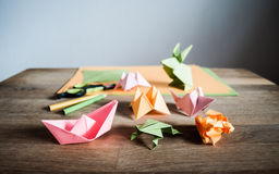 Origami figures, scissors and pencils on wooden table. Several origami figurines - flower, mouse, rabbit, frog and boat with some colored paper, scissors and Stock Photo