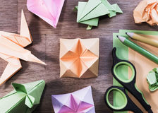 Origami figures on wooden table - flat lay, high angle view. Origami figurines - flower, swallow, rabbit, frog and boat with some colored paper, scissors and Royalty Free Stock Images