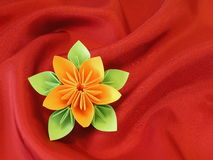 Origami flower. Orange origami flower on red satin stock photos