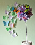 Origami flower ball. Origami kusudama flower ball and pastel coloured paper and artificial butterflies stock image