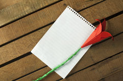 Origami flower and white paper sheet Royalty Free Stock Photo