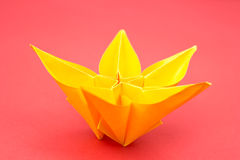 Origami flower. Yellow paper origami flower on red background Stock Photo