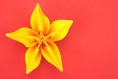Origami flower. Yellow paper origami flower on red background Stock Photos