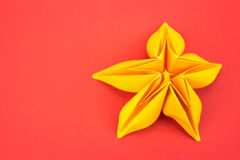 Origami flower. Yellow paper origami flower on red background Royalty Free Stock Image