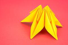 Origami flower. Yellow paper origami flower on red background Royalty Free Stock Images