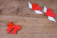 Origami hearts with wings on a wooden background. Two hearts Stock Image