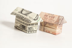 Origami house made of 1 dollar and Indian rupee banknotes. On white background Stock Photos