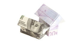 Origami house made of 500 euro and 100 dollar banknotes Royalty Free Stock Image