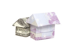 Origami house made of 500 euro and 100 dollar banknotes Stock Photo