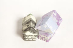 Origami house made of 500 euro and 100 dollar banknotes Stock Photography