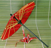 Origami and Japanese umbrella 2. A paper Japanese figurine and aJapanese umbrella sugestion on a bamboo floor Royalty Free Stock Photography