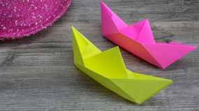 Origami, kleurrijke boten en roze hoed op houten achtergrond, hobby stock afbeeldingen