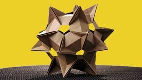 Origami kosmisch cijfer aangaande gele achtergrond stock video