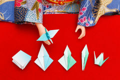 Origami lesson. A Japanese doll dressed in kimono showing the steps to fold a paper bird Royalty Free Stock Images