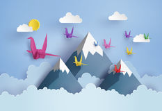 Origami made colorful paper bird flying on blue sky Royalty Free Stock Photography