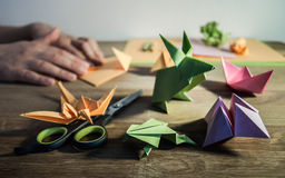 Origami making - figures and hands on wooden table. Origami figurines - flower, swallow, rabbit, frog and boat with some colored paper, scissors and pencils. In Royalty Free Stock Photos