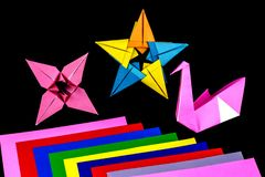 Origami Models and Coloured Paper on a Black Background. Paper origami models and coloured paper isolated against a black background royalty free stock photography