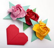 Origami a multi colored roses. Green leaves and red heart royalty free stock image