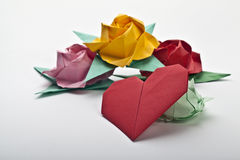 Origami a multi colored roses. Green leaves and red heart stock image