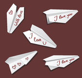 Origami paper airplane toy white on red labeled I love you Royalty Free Stock Image