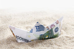 Origami paper boat of euro notes on sand Royalty Free Stock Images