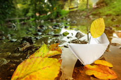 Origami paper boat sailing from summer to aut Stock Photo