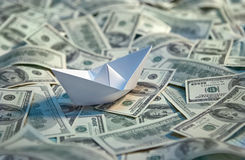 Origami paper boat at sea of money. Studio photography of american moneys of hundred dollar on background Stock Image