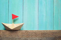 Origami paper boat. On a wooden background, summer travelling concept royalty free stock photography