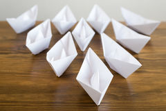 Origami paper boats on a wooden table Stock Photos