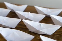 Origami paper boats on a wooden table Royalty Free Stock Photos