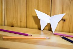 Origami, paper butterfly on a wood shelf with colored pencils stock photography