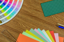 Origami paper, colorful paper, cutting mat and pencil on wooden table Royalty Free Stock Image