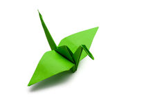 Origami paper crane. Green origami paper crane on white paper background stock photography