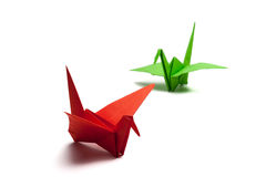 Origami paper crane. Red and green origami paper crane on white paper stock image