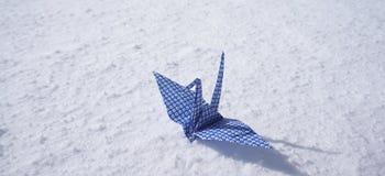 Origami paper crane on white snow floor Stock Photography