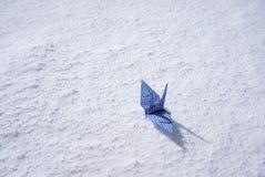 Origami paper crane on white snow floor Stock Photo