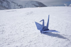 Origami paper crane on white snow floor Royalty Free Stock Photography