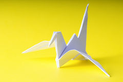 Origami paper crane on yellow. Background royalty free stock images