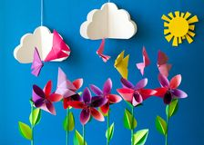 Origami paper flowers, butterflies, clouds and sun.