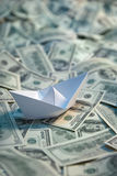 Origami paper ship at sea of money Stock Photo