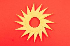 Origami paper sun isolated on red background Stock Photo