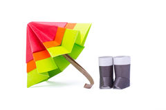 Origami paper umbrella. Multicolor with gumboots on a white background Royalty Free Stock Photo