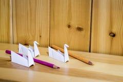 Origami papperskran på en wood hylla med kulöra blyertspennor fotografering för bildbyråer