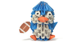 An origami penguin lays with a football. Royalty Free Stock Photo