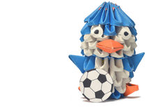An origami penguin plays with a soccer ball. Royalty Free Stock Image