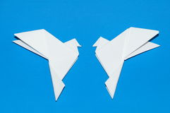 Origami pigeons on a blue background. Royalty Free Stock Images