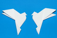 Origami pigeons on a blue background. Stock Photos