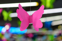 Origami pink butterfly against the backdrop of neon bokeh Stock Image