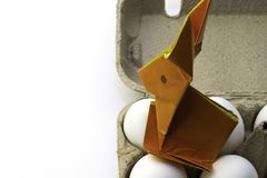 Origami rabbit from orange colored paper. Easter bunny and white chicken eggs in a box, copy space royalty free stock image