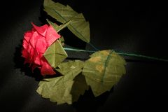 Origami rose in dark background. Origami rose spotlighted on a dark background Royalty Free Stock Photography